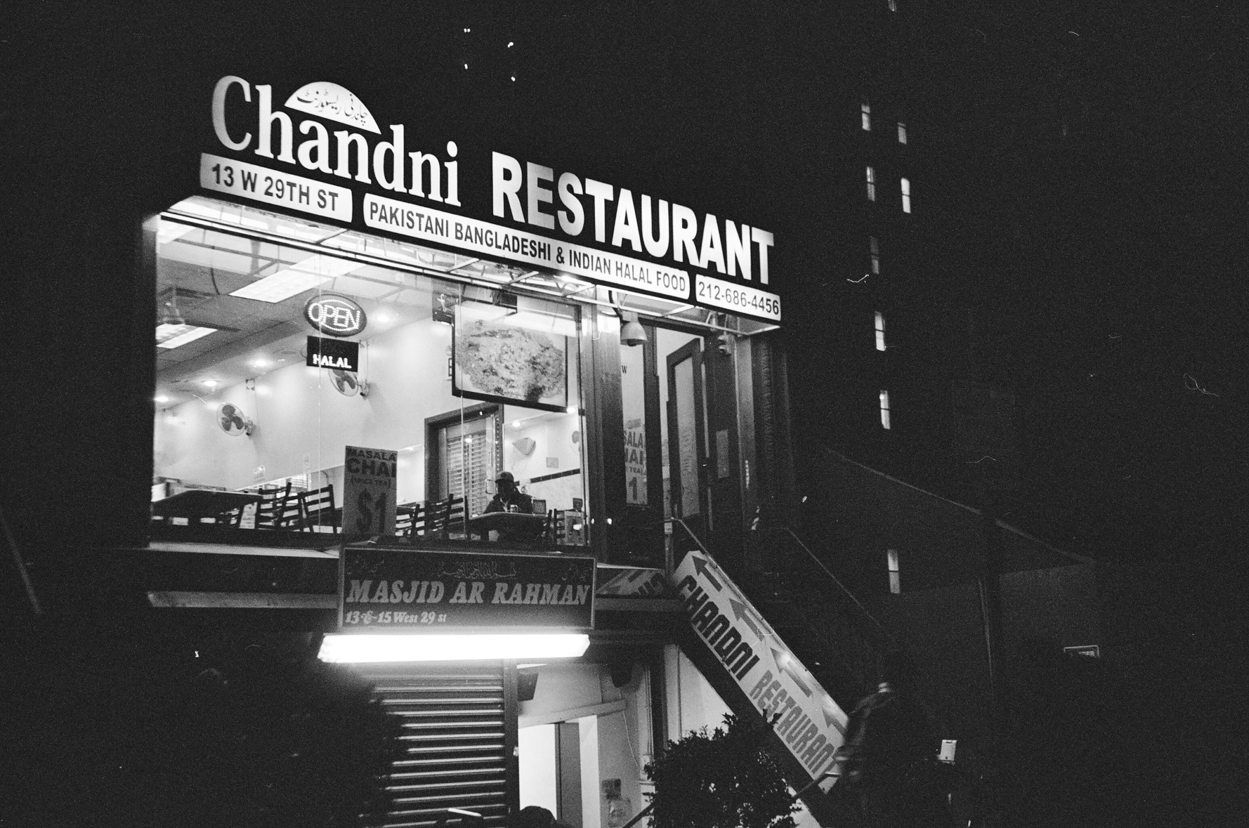 Black and white photo of Chandi Restaurant at night. There is a man in the window of the restaurant, he is seated at a table with his meal.