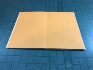 A beige soft cover drum leaf book is open flat on a cutting board.