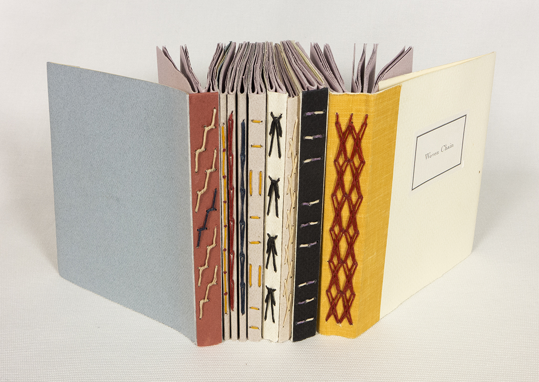 Colorful spines of 1, 2, & 3 section books are lined next to each other. The spines are a range of colors and the thread seen along them is decorative.
