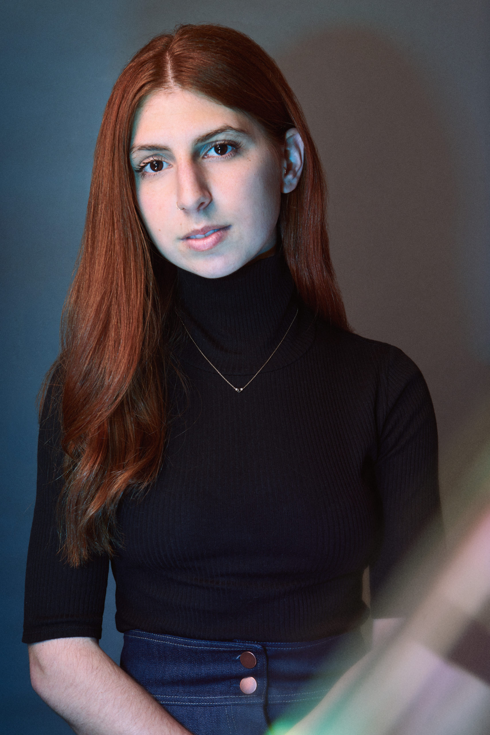 fair skin woman with long red hair in a black turtleneck