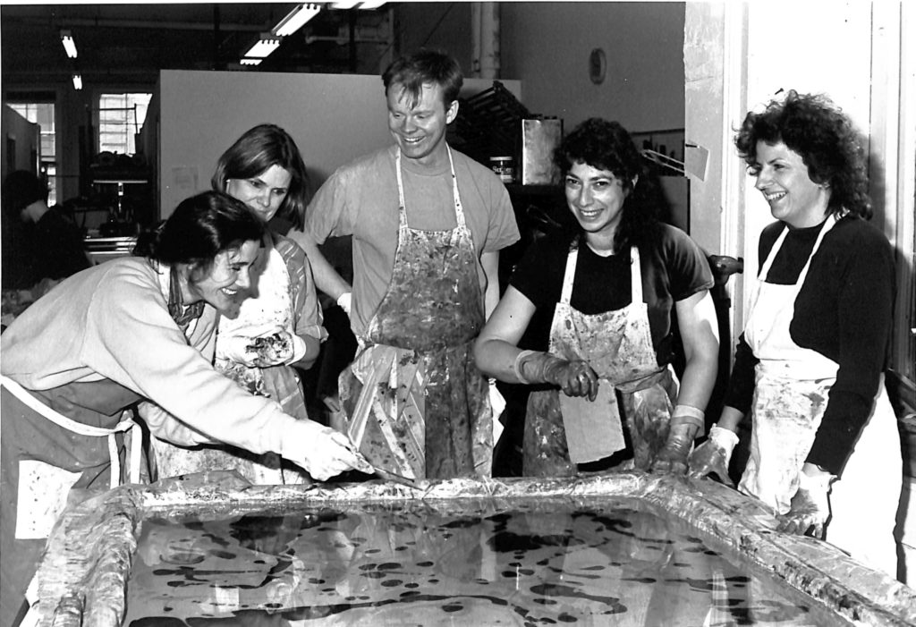 A black and white image of four women and one man in stained aprons working over a wide tray of water and ink to marble paper. They are all smiling.
