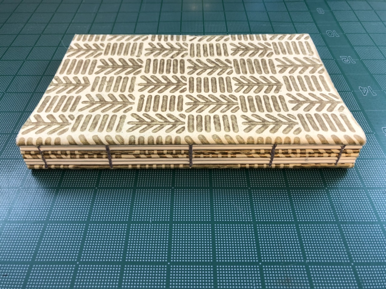Patterned coptic notebook placed on a cutting mat.