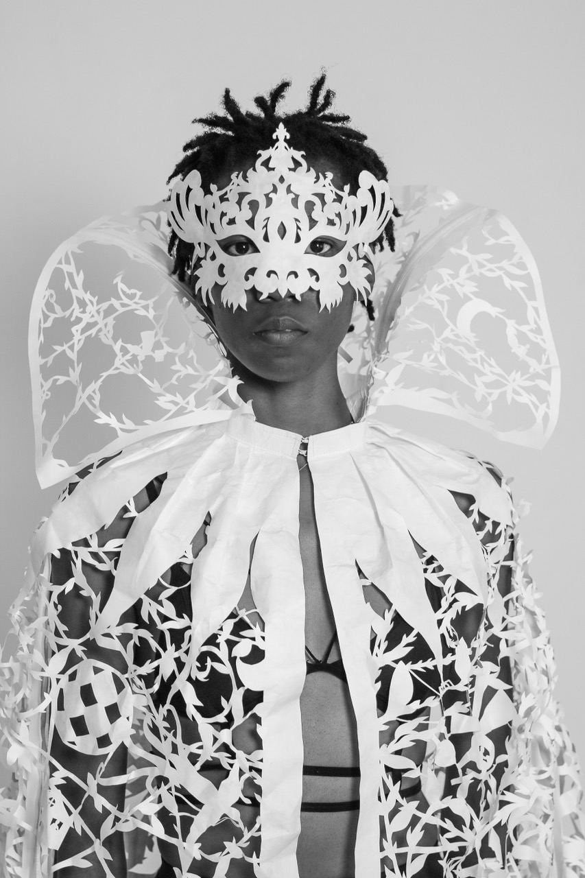 A person is dressed in a papercut cape, wings, and masquerade mask done by Beatrice Coron. The photo is in black & white.