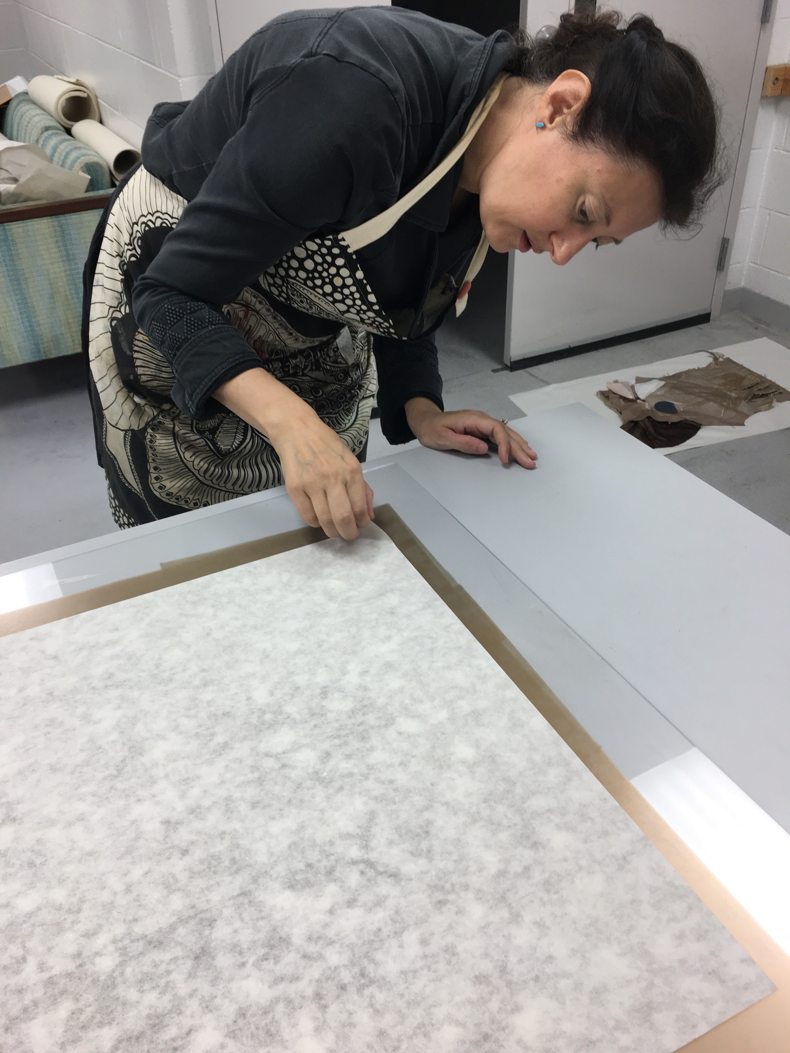 Image of Denise closely investigating prints on a table