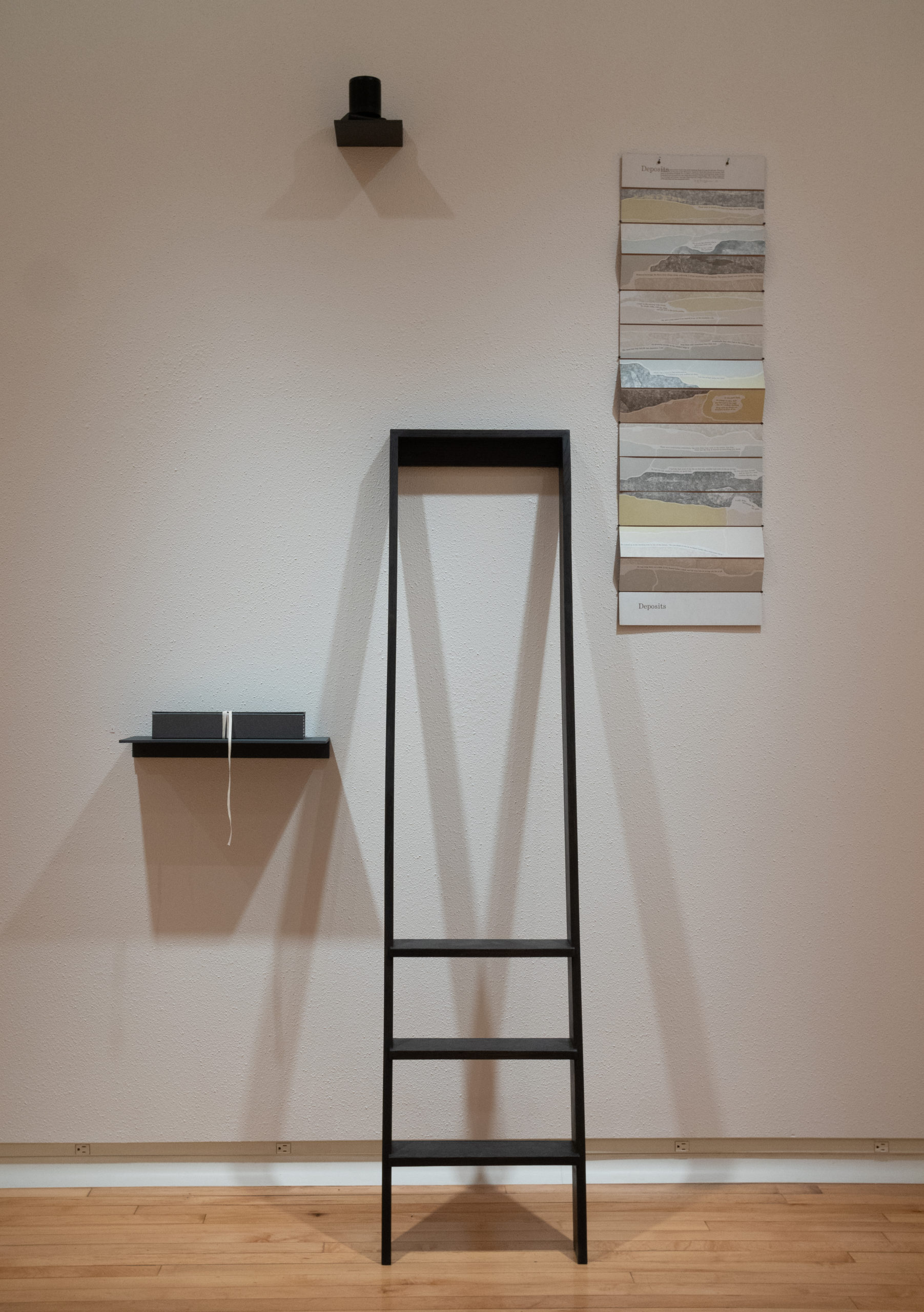 ladder leans against the wall with accordion artist's book hanging beside it