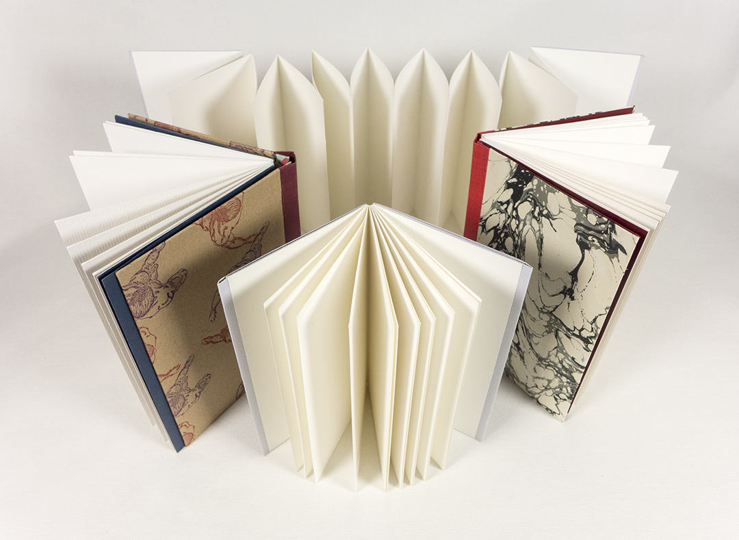 Several drum-leaf bound books are placed next to each other. One of the examples is more of an accordion fold while the other three are full hardcovers.