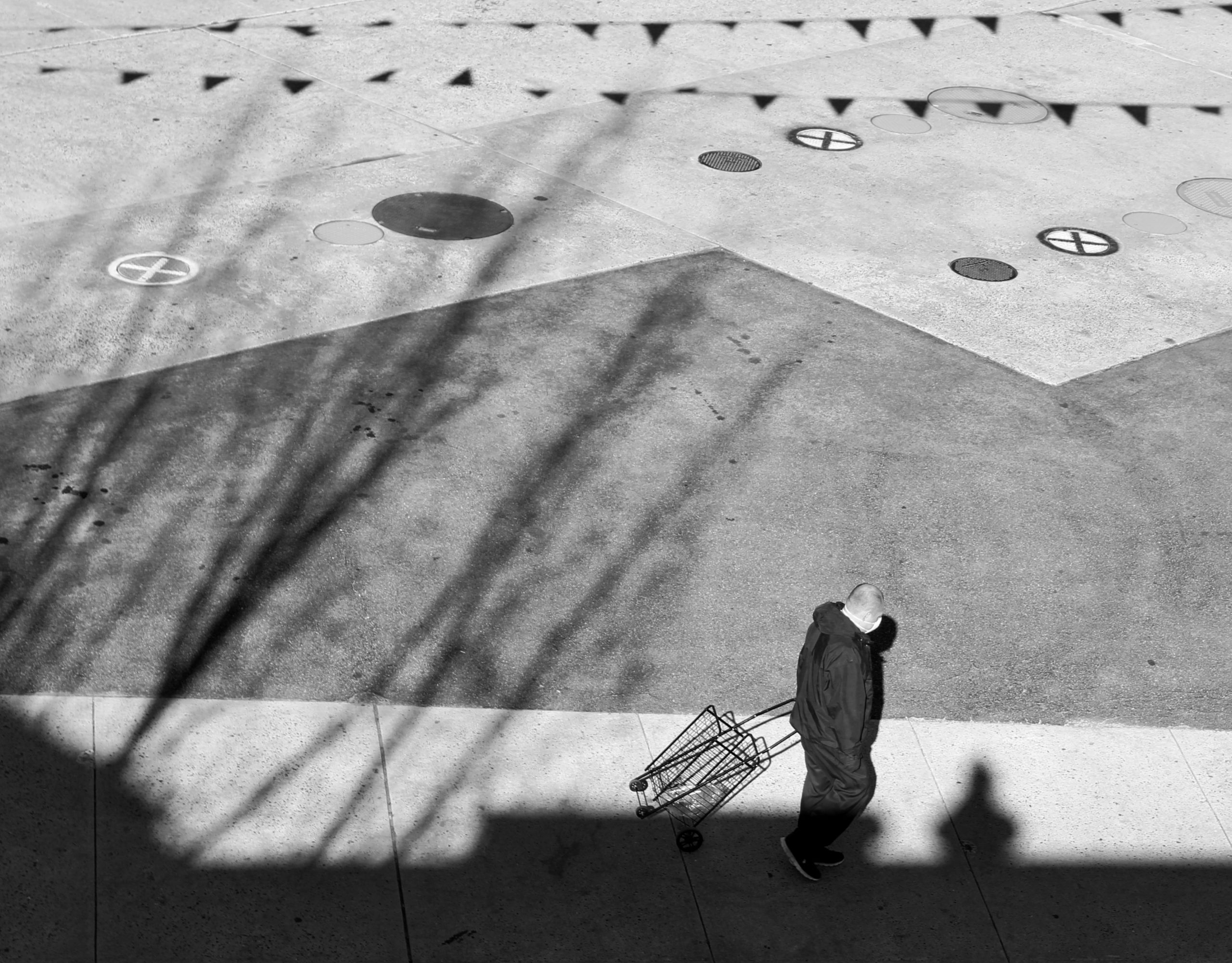 Black and White photograph taken from the rooftop, of a man walking among shadows spread across the ground