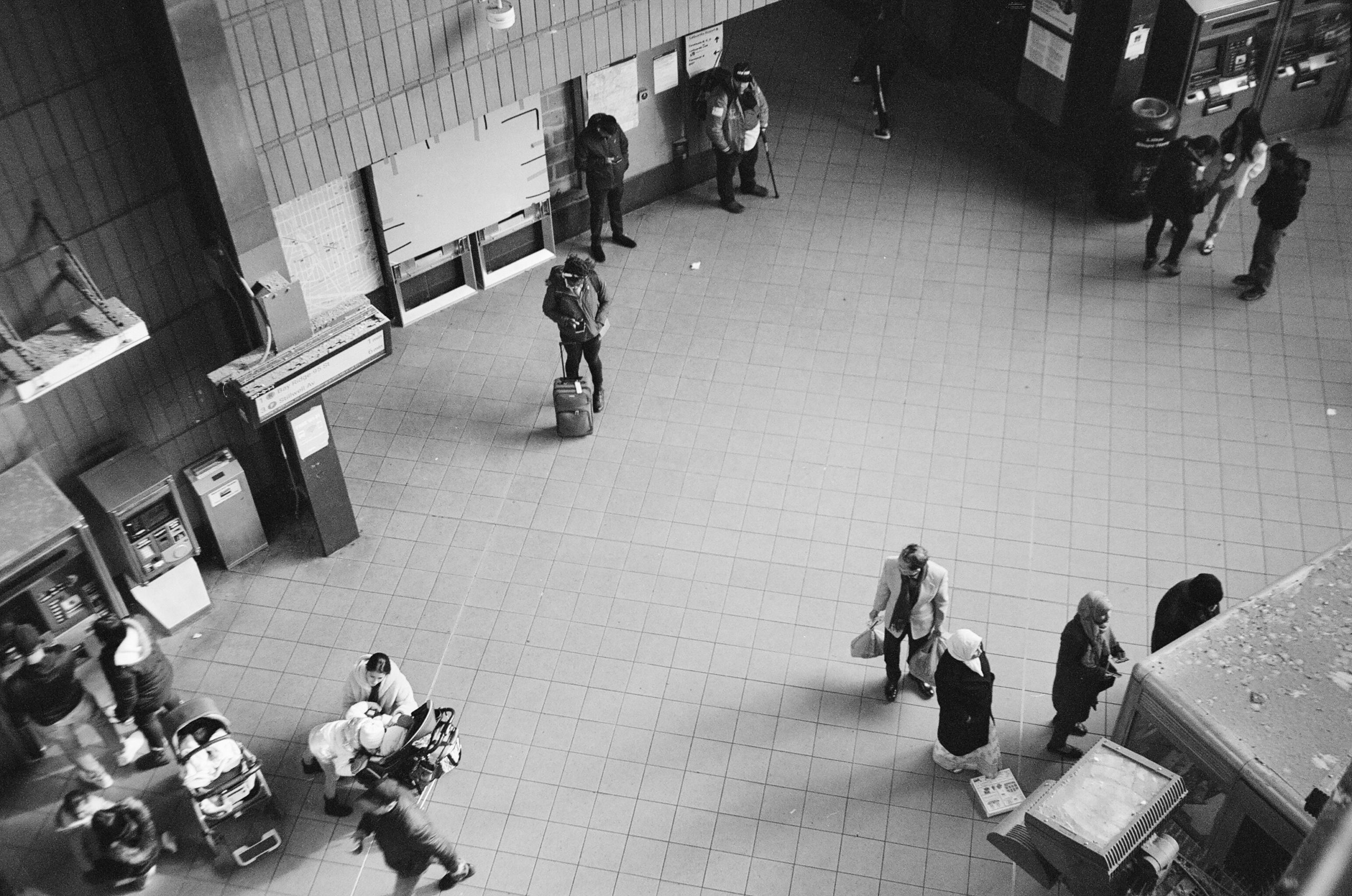 Black and white photo of the hustle&bustle in the Jackson Heights Roosevelt Ave. Station,