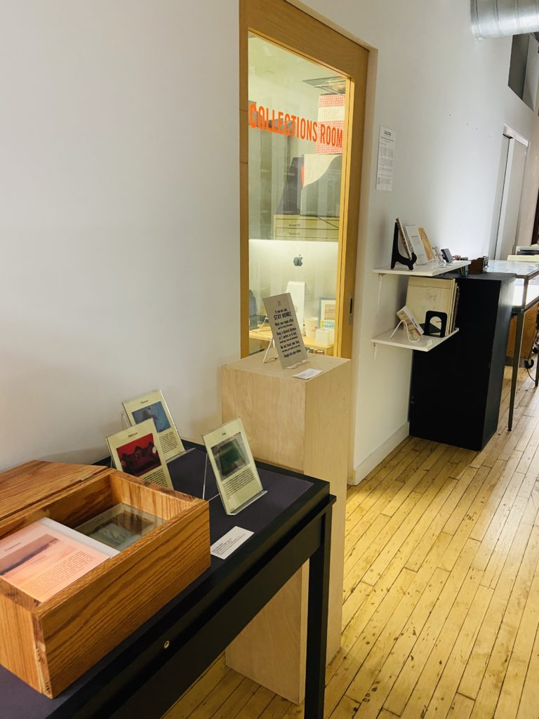"A photo of our collections hallway with a view of a door that reads ""COLLECTIONS ROOM"" in orange lettering. There are several tables, shelves, and plinths with books displayed."