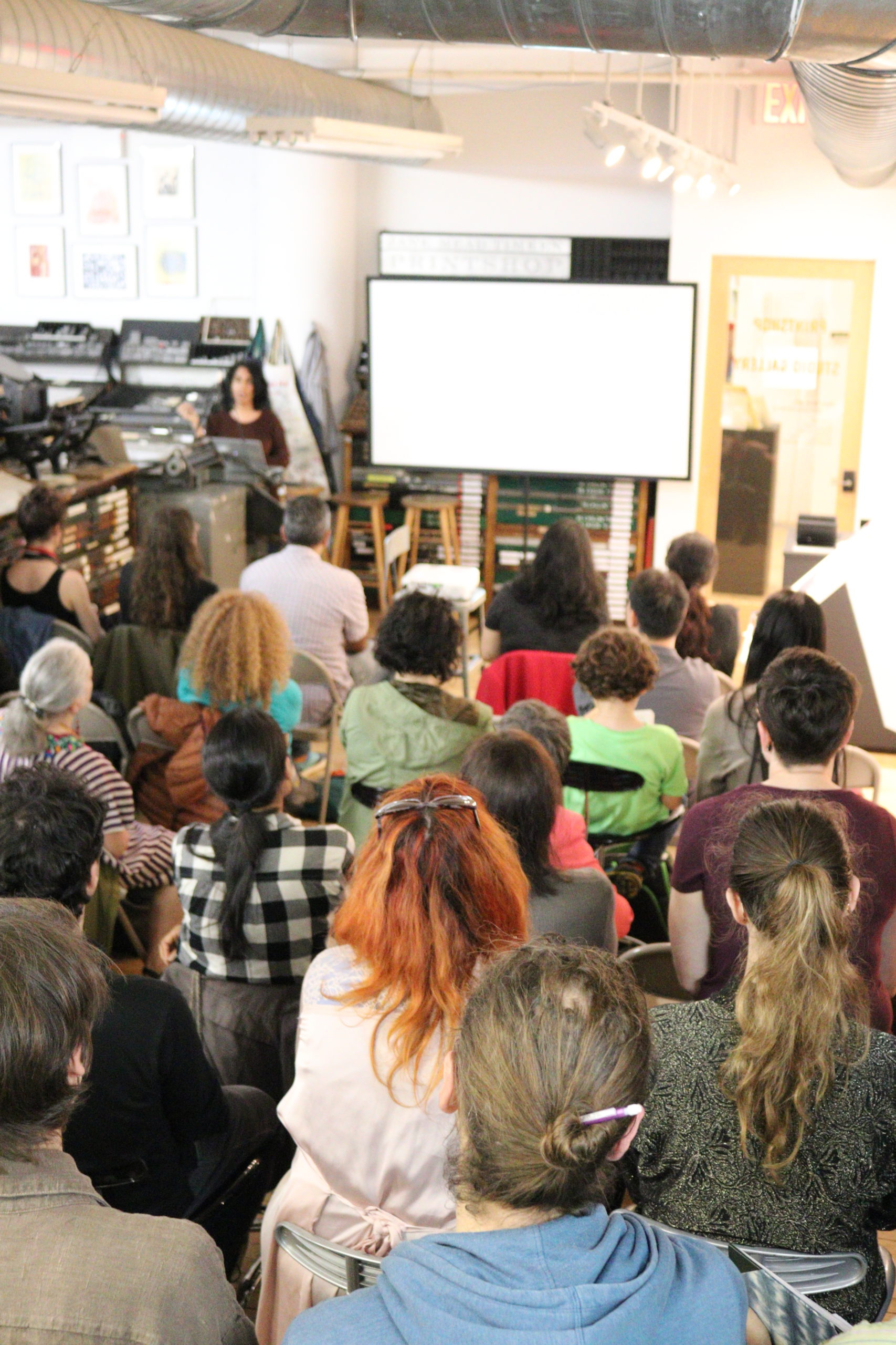 Shelly, a medium skin woman with wavy black hair speaks to a crowd of people in the cba printshop