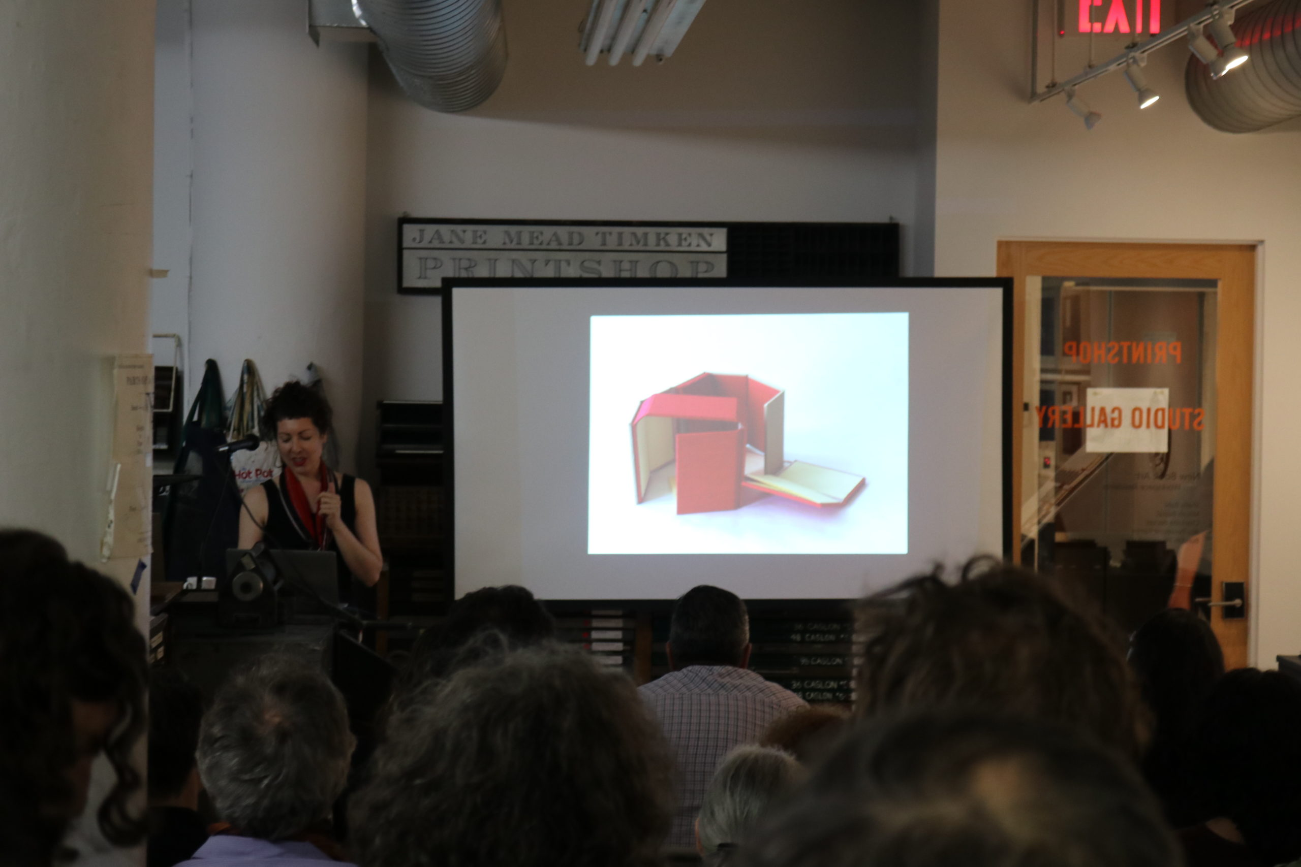 Milcah Basel speaks to a crowd of people in the cba printshop