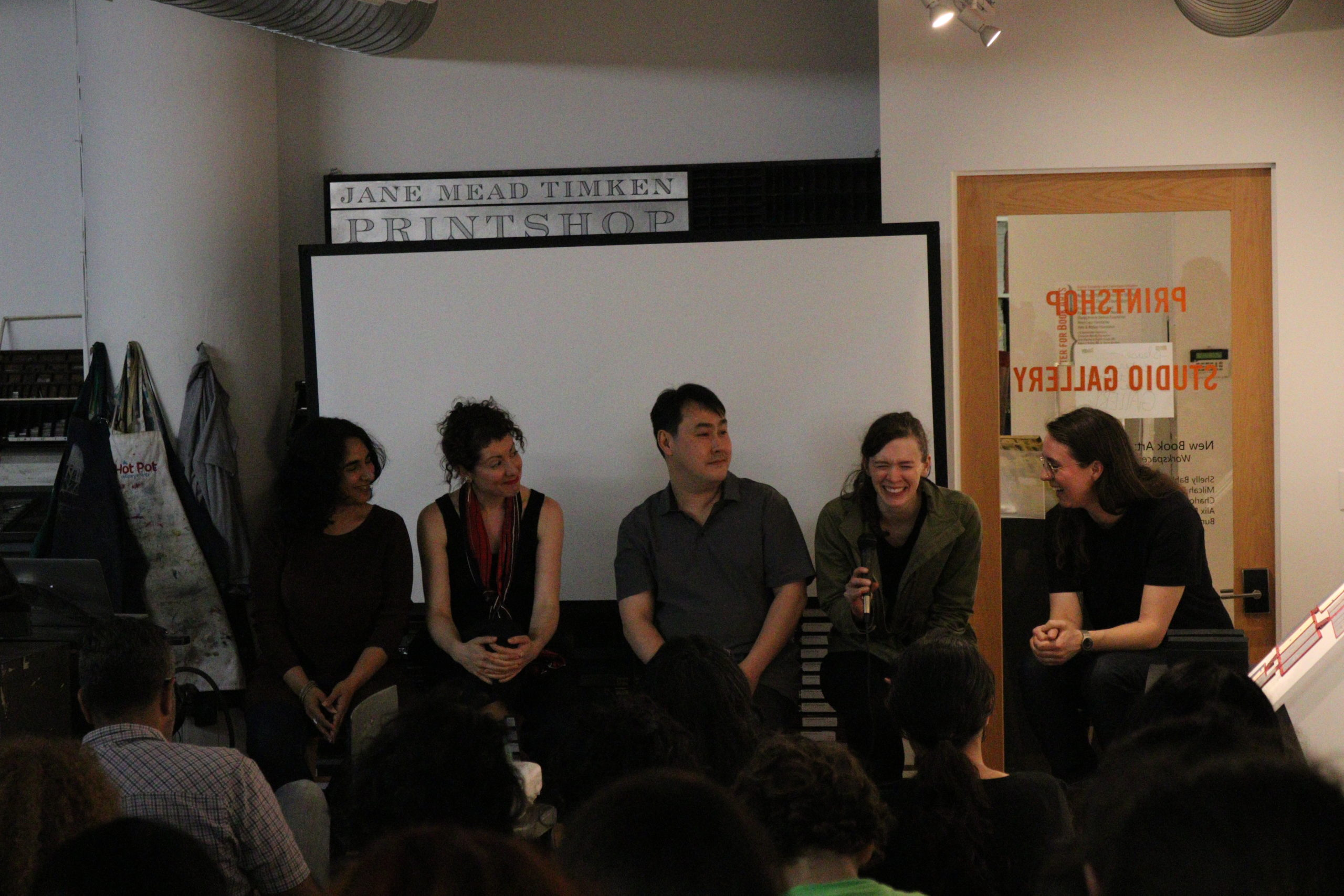 Shelly, Milcah, Bundith, Alix, and Charlott sit in front of a large audience