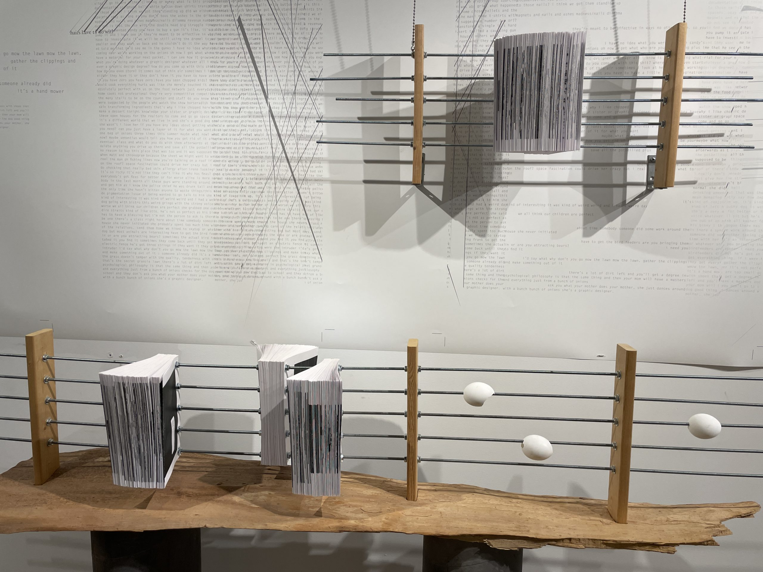 books pierced with metal rods and eggshells