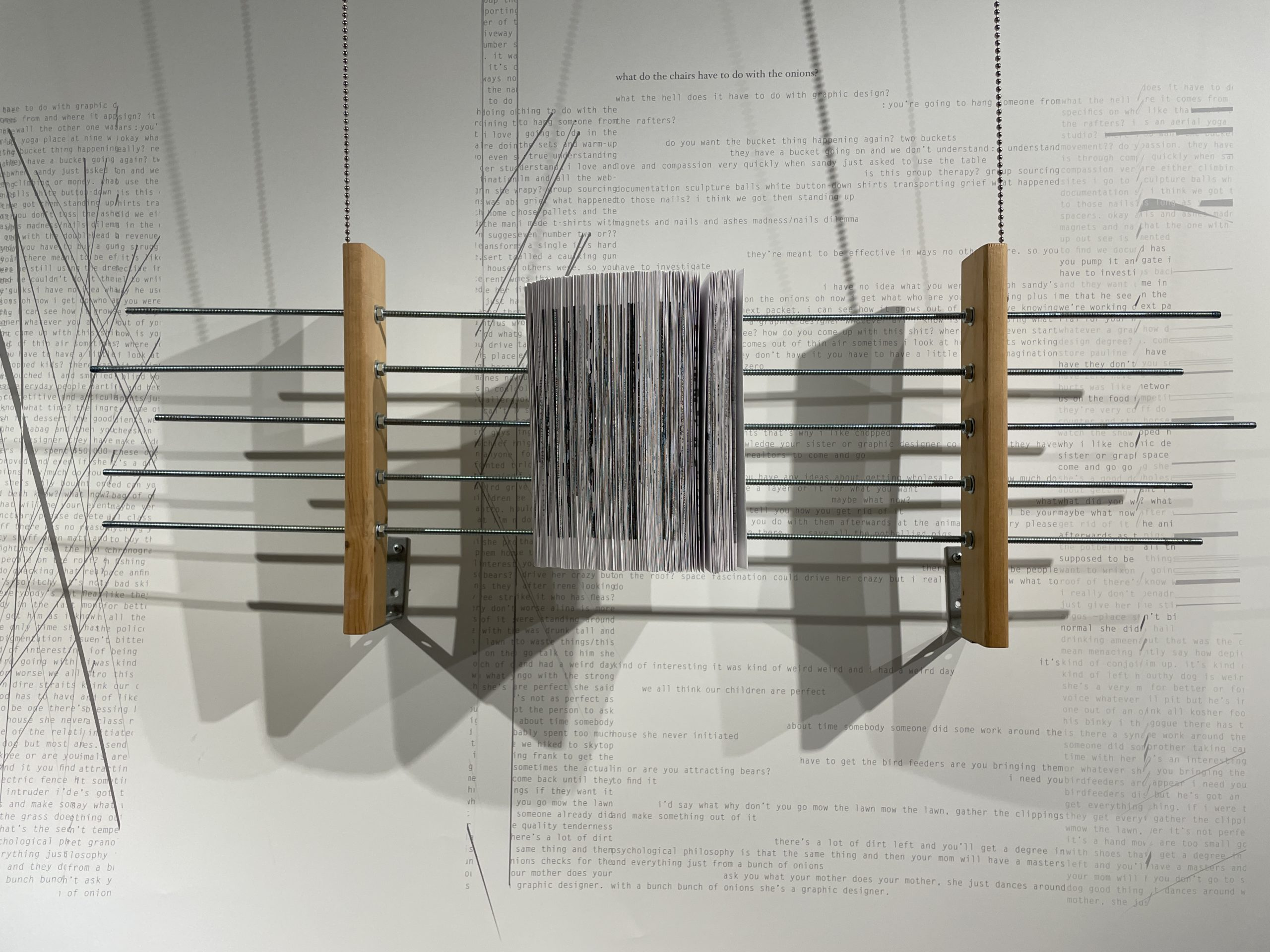 book pierced by metal rods hanging in front of a wall