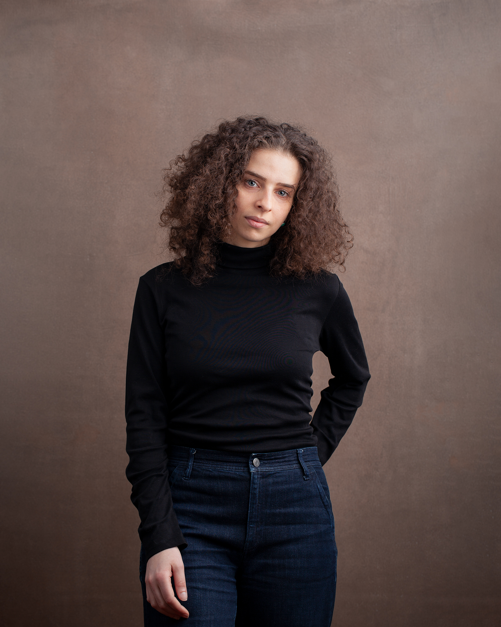 Jenna is posing with one hand in her back pocket and the other hand at her side, staring directly in the camera. She is wearing a black turtleneck and dark blue jeans, and has a copper colored backdrop.