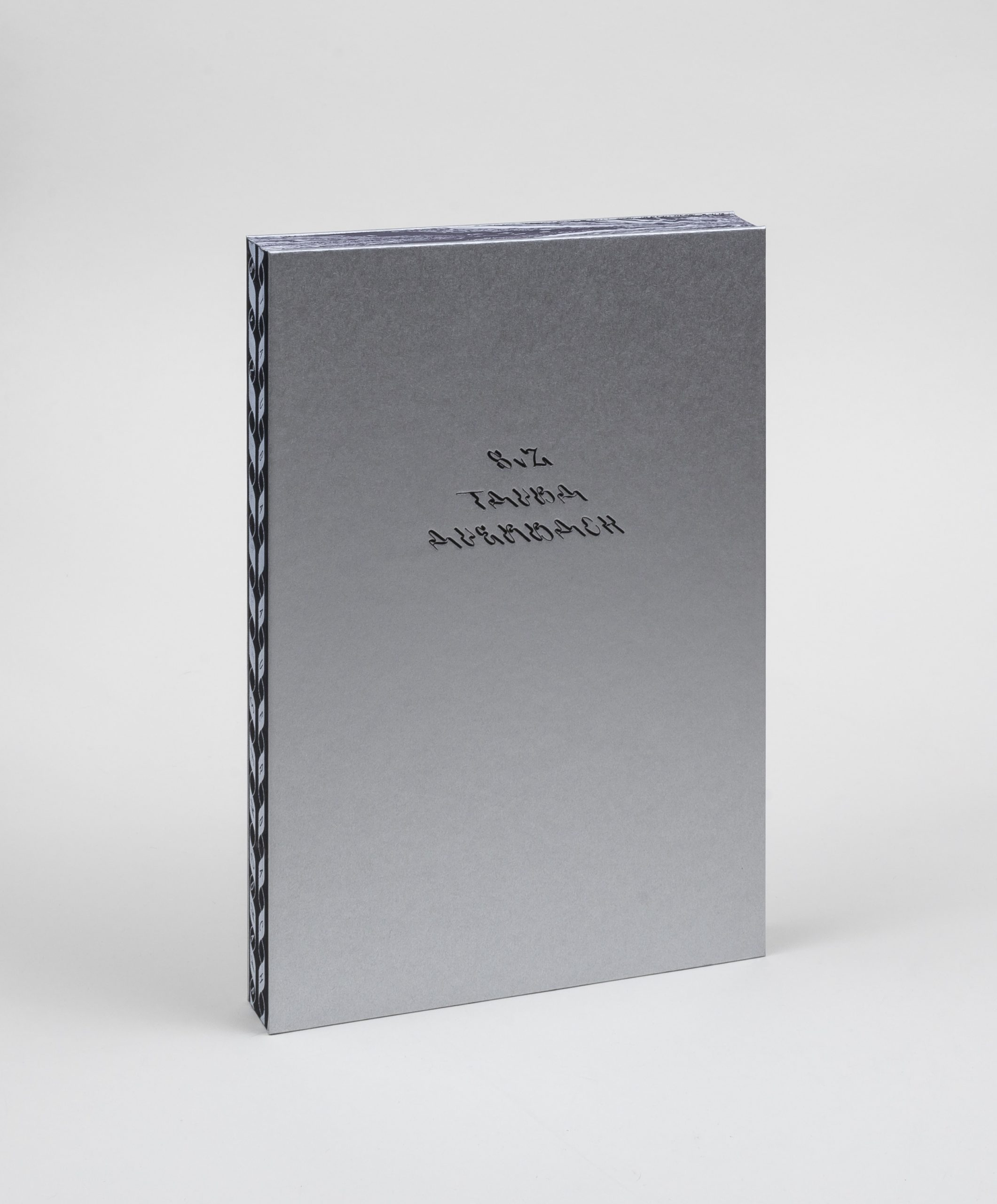 "Image of a book standing upright. The book has a silver cover with ""S v Z Tauba Auerbach on the cover"