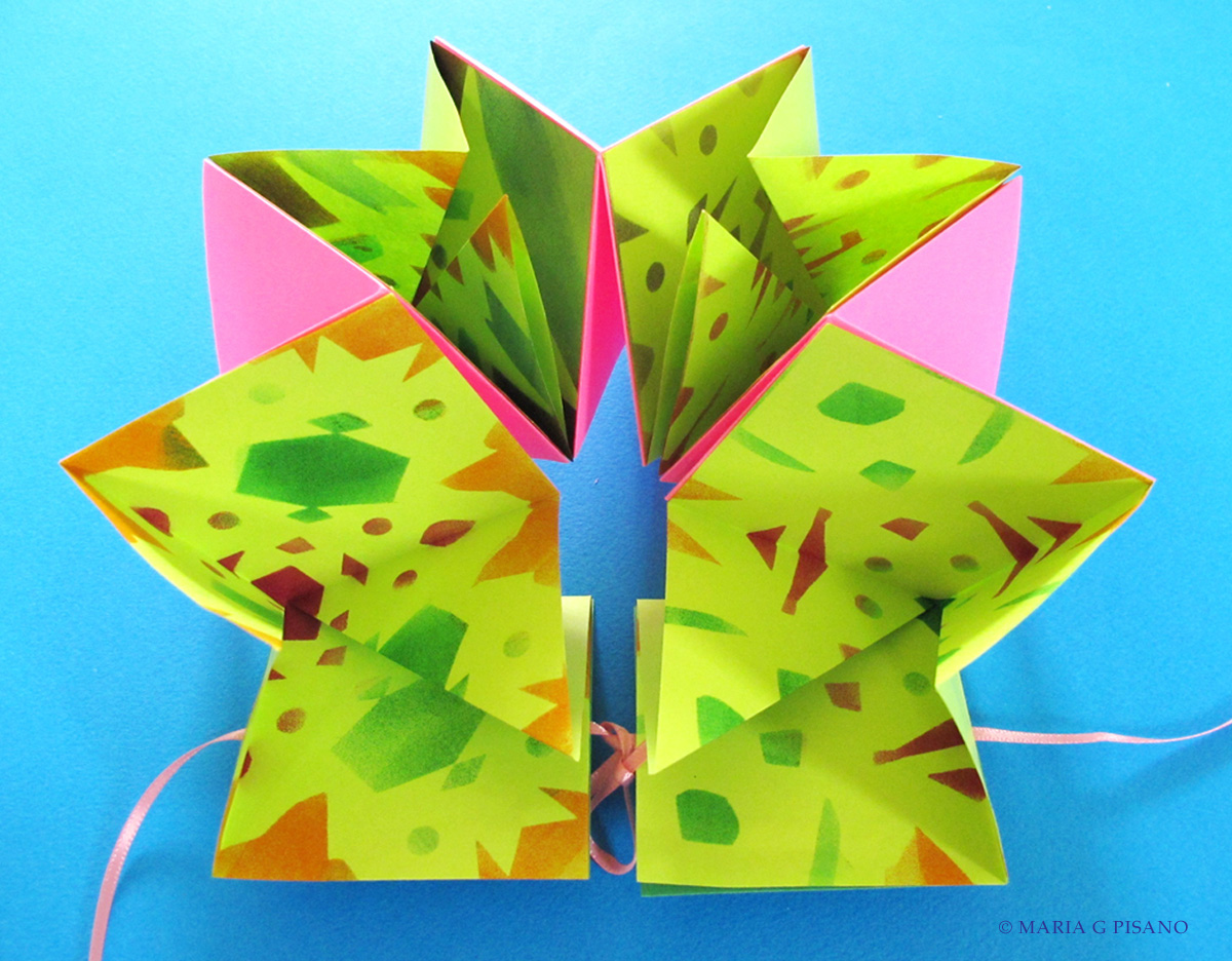 A bright green, orange, and pink flexagon book by Maria Pisano. The book is open in front of a blue background.