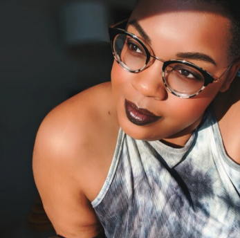 medium skin black woman with glasses in a tie-dye tank top