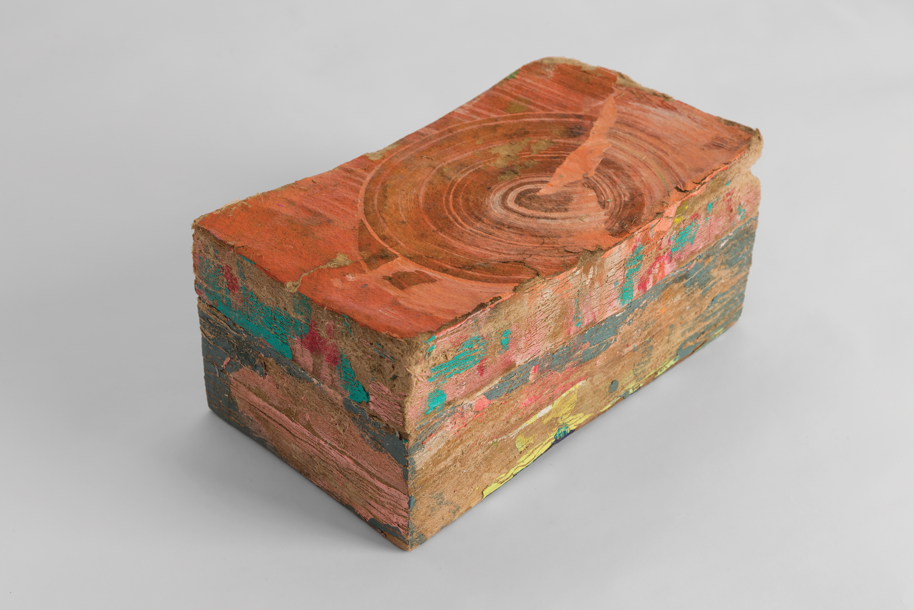 What appears to be a rectangular block of wood spattered with multiple colors of paint