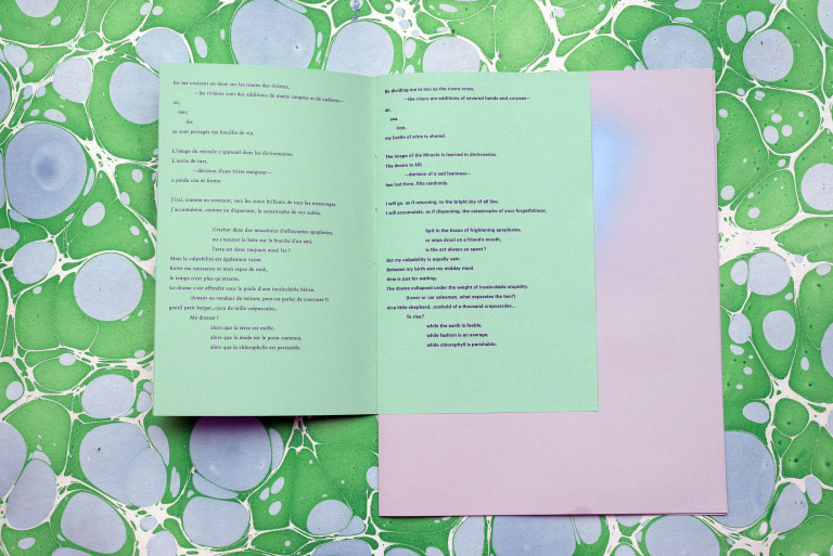 Chapbook bound with multiple sizes of paper, set against a marbled paper background.