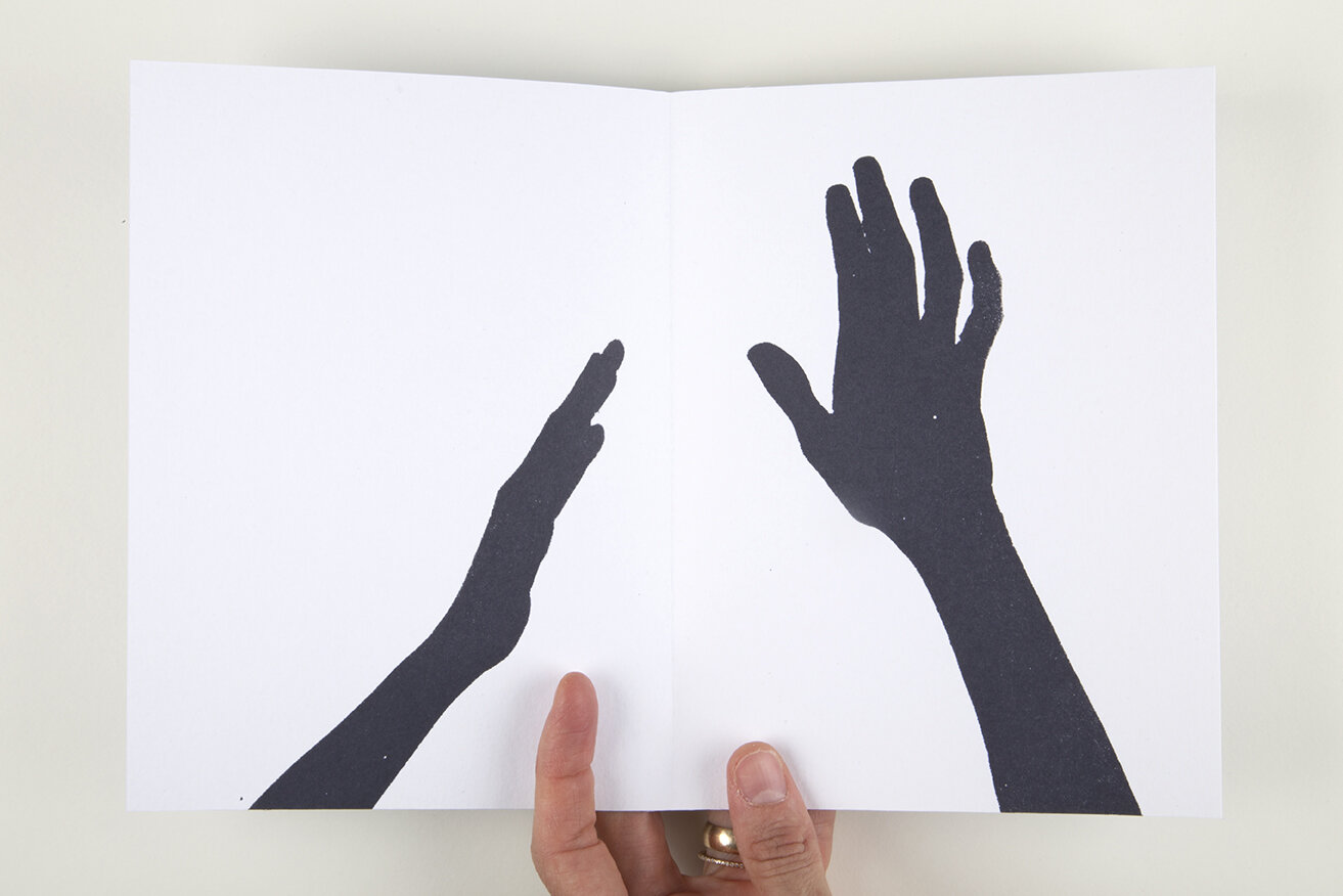 Open white book over white background. On the left page there is a black hand trying to reach an open black hand on the right page.