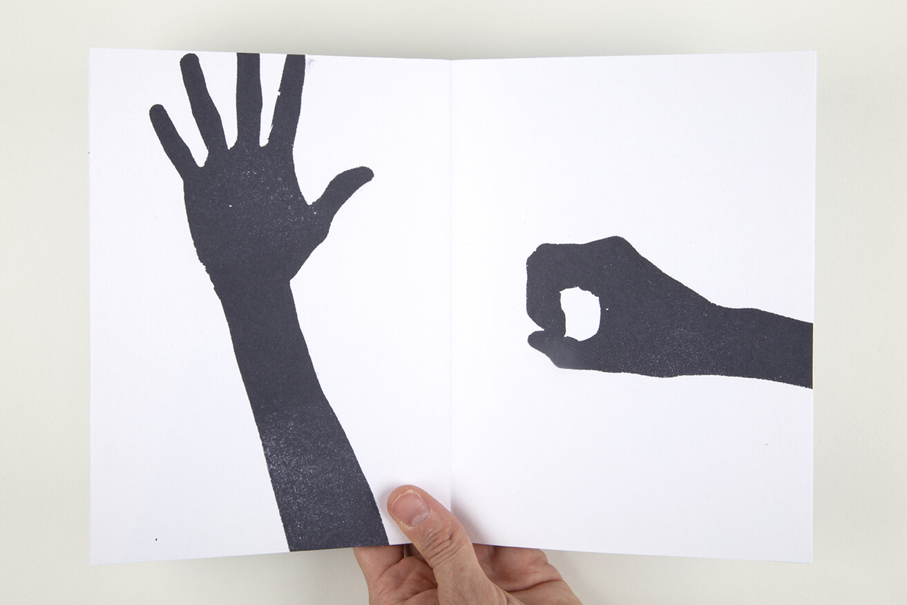 Open white book over white background. On the left page there is a black hand trying to reach another hand on on the right page.