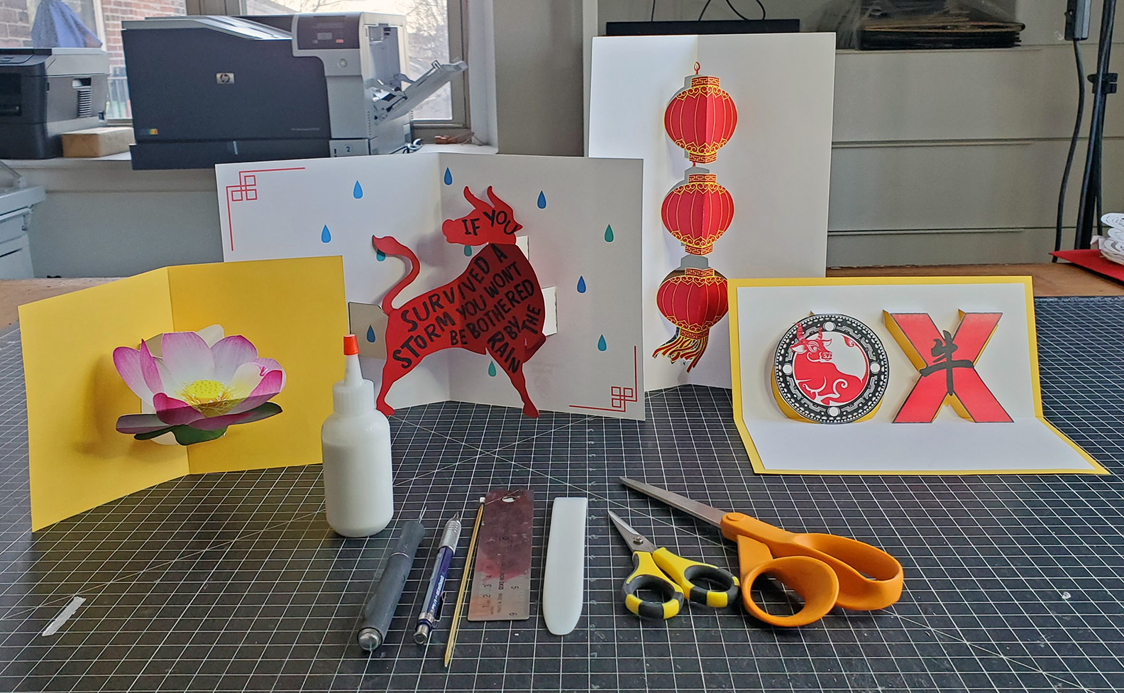 Standing upright on a table are colorful year of the Ox themed pop-up cards. Supplies sit neatly in front of the work.