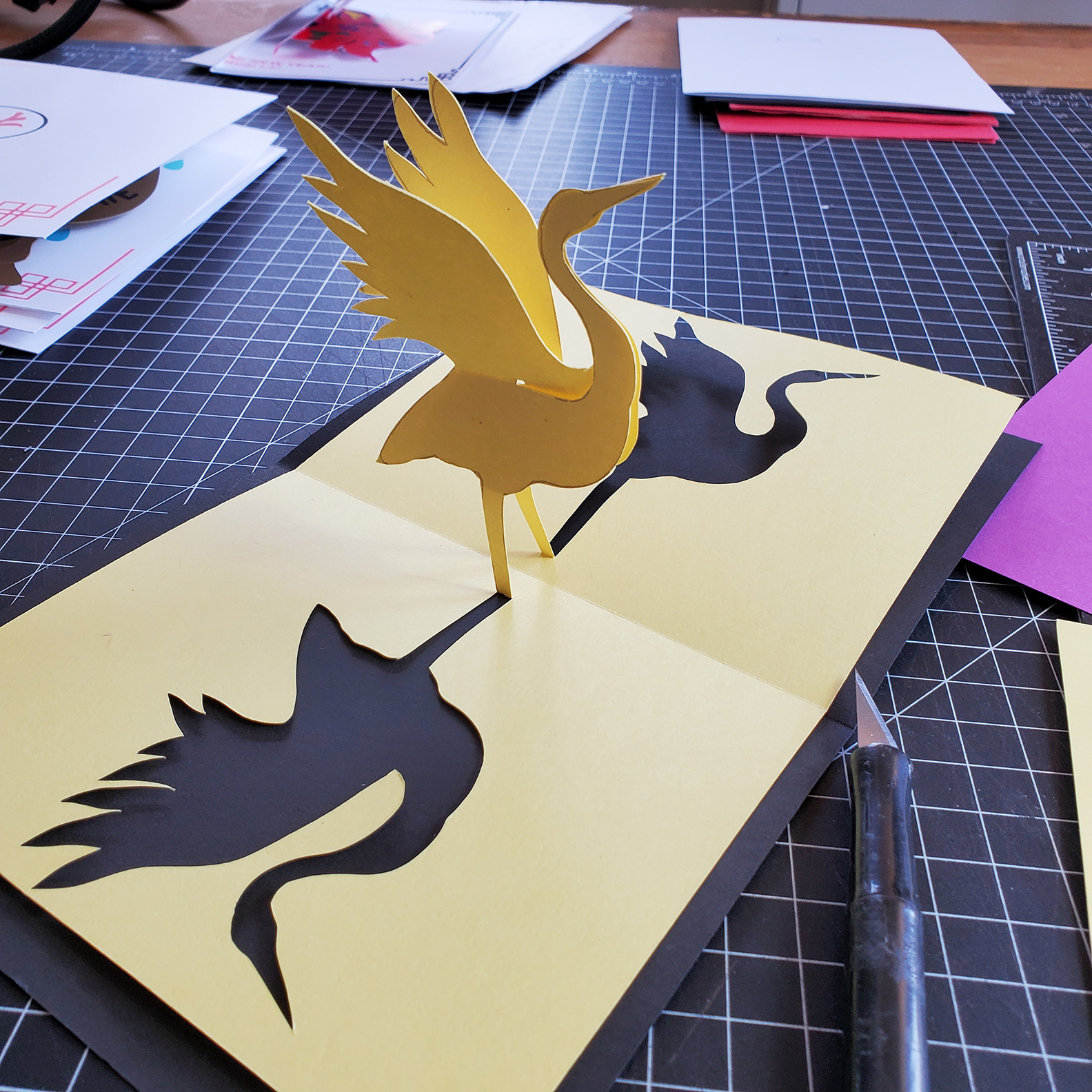 A yellow crane pop-up book is laid flat on a work table.