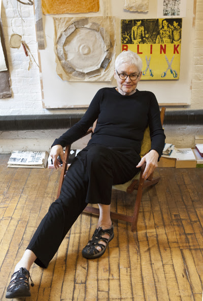 grey haired woman dressed in black lounging in a chair looking directly at the viewer