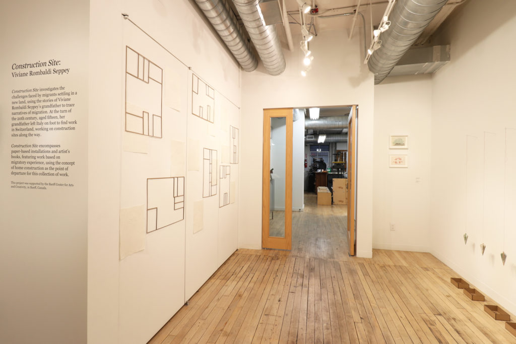 Installation view of Construction Site by Viviane Rombaldi Which has hanging artworks on both sides of the image, a vinyl description on the far left, and a door into the bindery straight ahead.