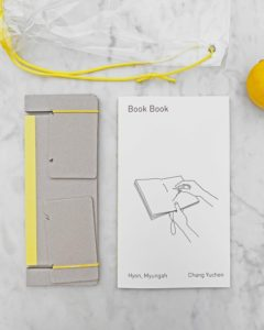 Book Book by Chang Yuchen & Hyon, Myungah. White book cover with black text, laying next to a hole-punching cradle.