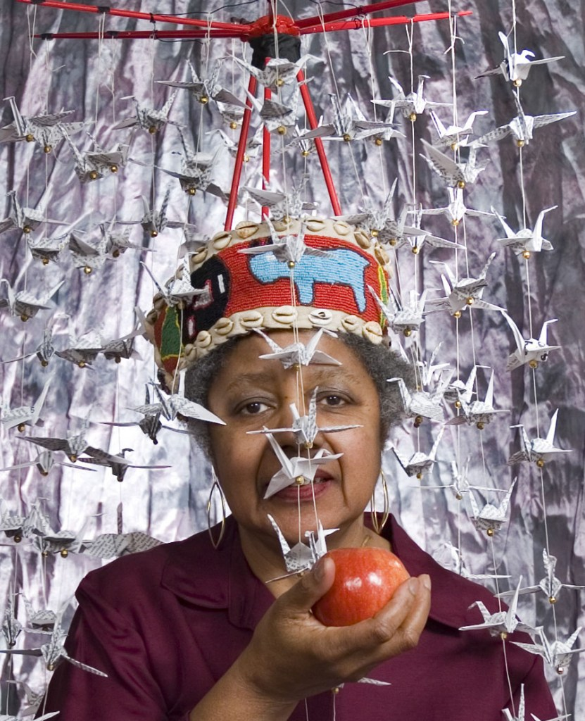 A self portrait of Clarissa Sligh depicting a photo of an older Black woman with a cropped haircut. She is holding an apple and is surrounding by white paper cranes. She is wearing a red felt crown.
