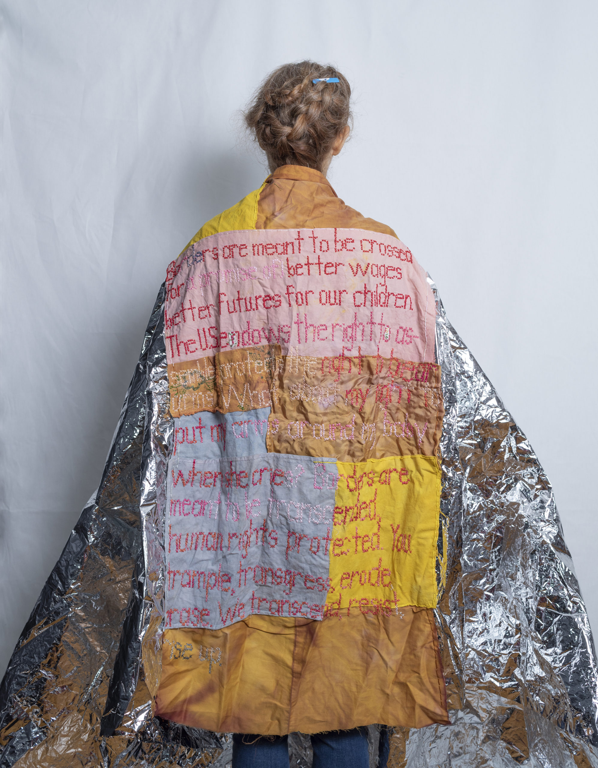 Image of a person draping a tapestry around their shoulders