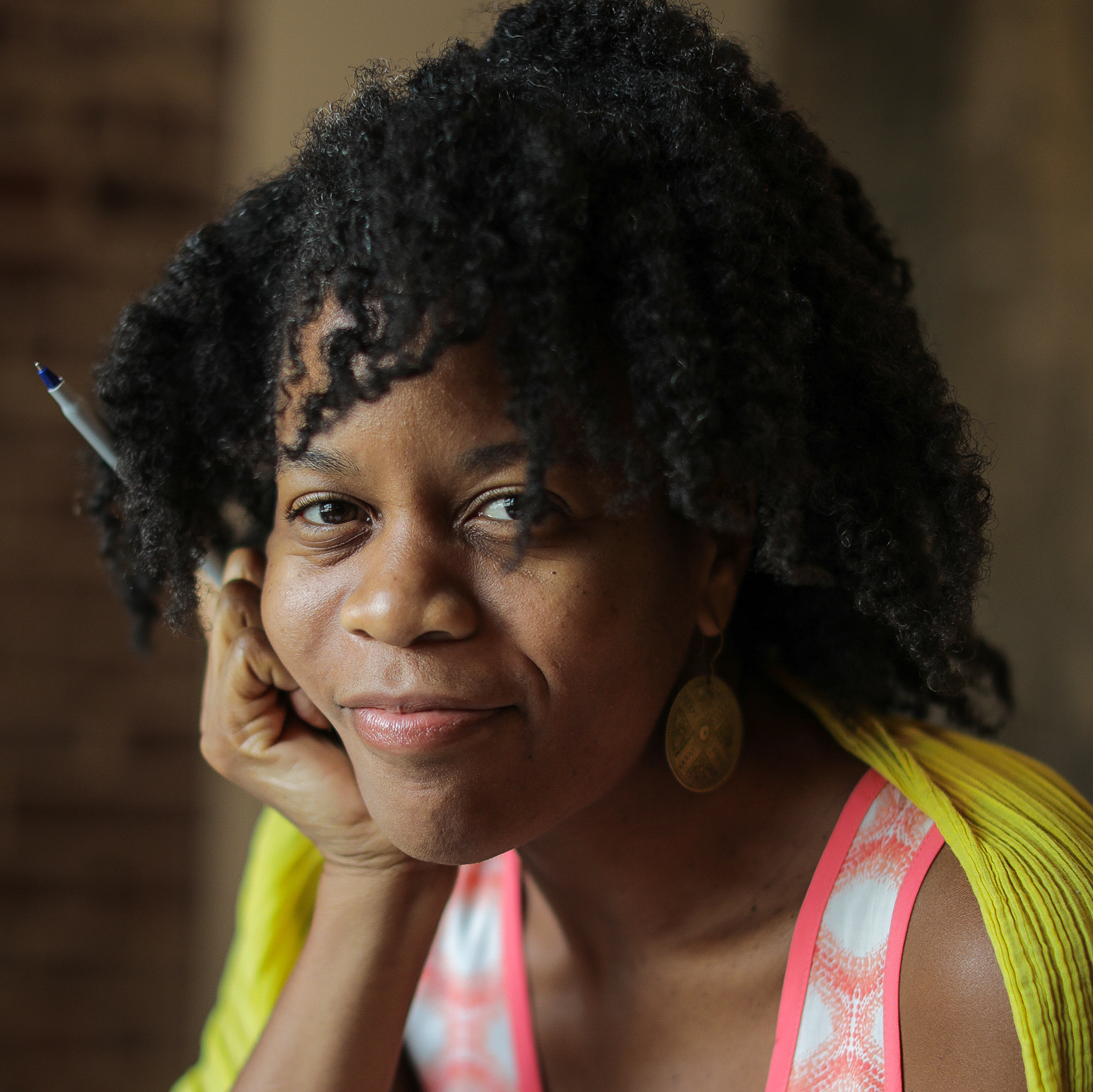 Portrait of woman with a yellow cardigan draped around her shoulders and a pink tank top underneath, she is resting her face on her hand, which is also holding a pen.