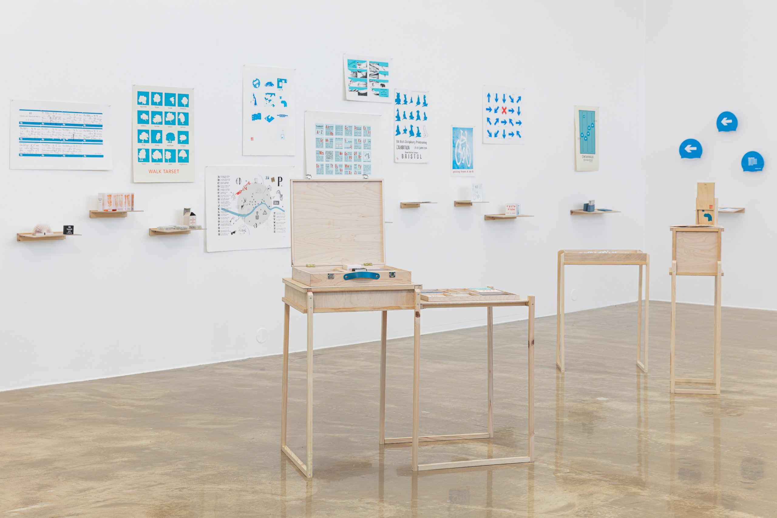 Image of a gallery installation, with a wooden briefcase sitting in the foreground, and an installation of prints in the background. The prints all consist of illustrations created with various shades of blue ink
