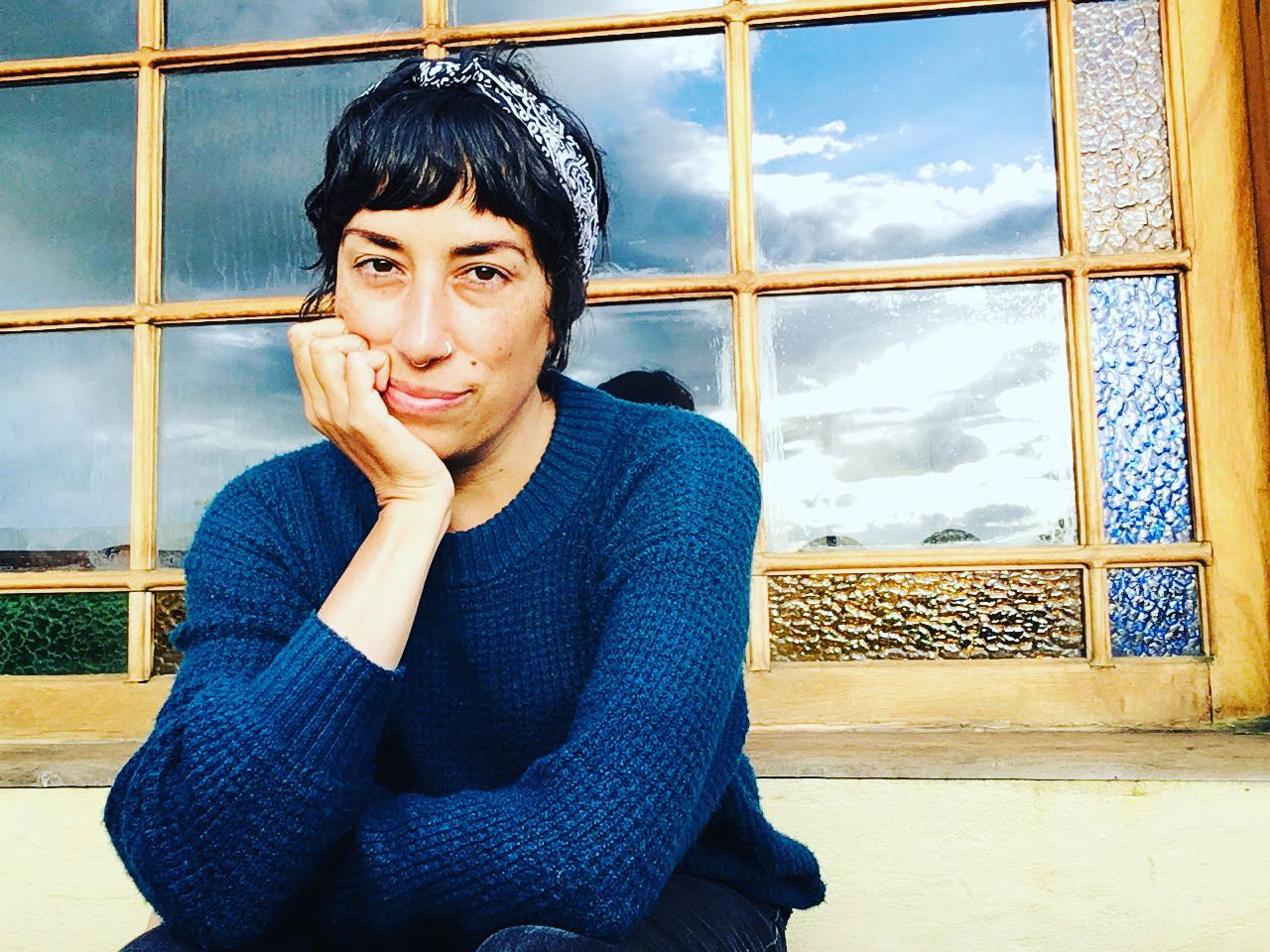 portrait of a person in a blue shirt and headband, sitting in front of a window reflecting a daytime sky, filled with clouds and sunlight
