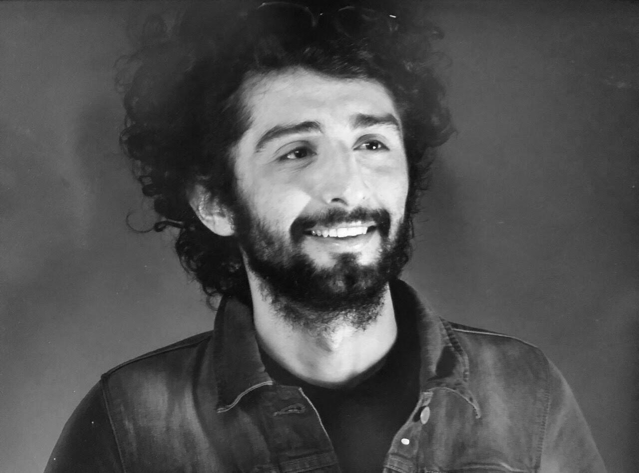 Black and White image of a man with a collared denim shirt, staring off with a smile on his face.