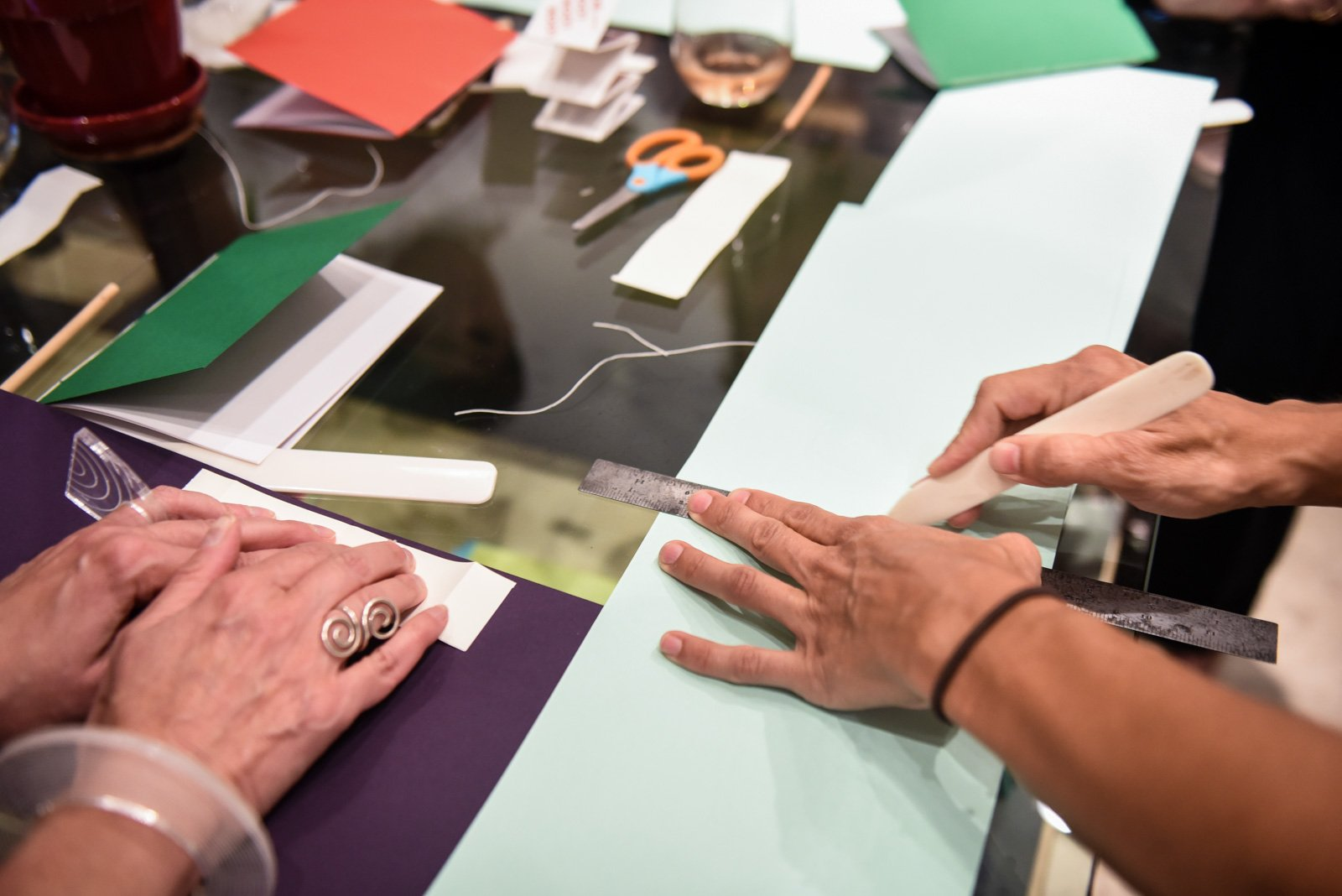 Two pairs of hands set on a table holding bone folders and folding paper.