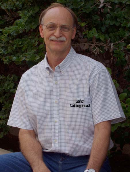 """Photo of John L. Risseeuw from his website, CabbageHead Press. He is wearing a short sleeve shirt with """"Senor CabbageHead"""" on the pocket."""