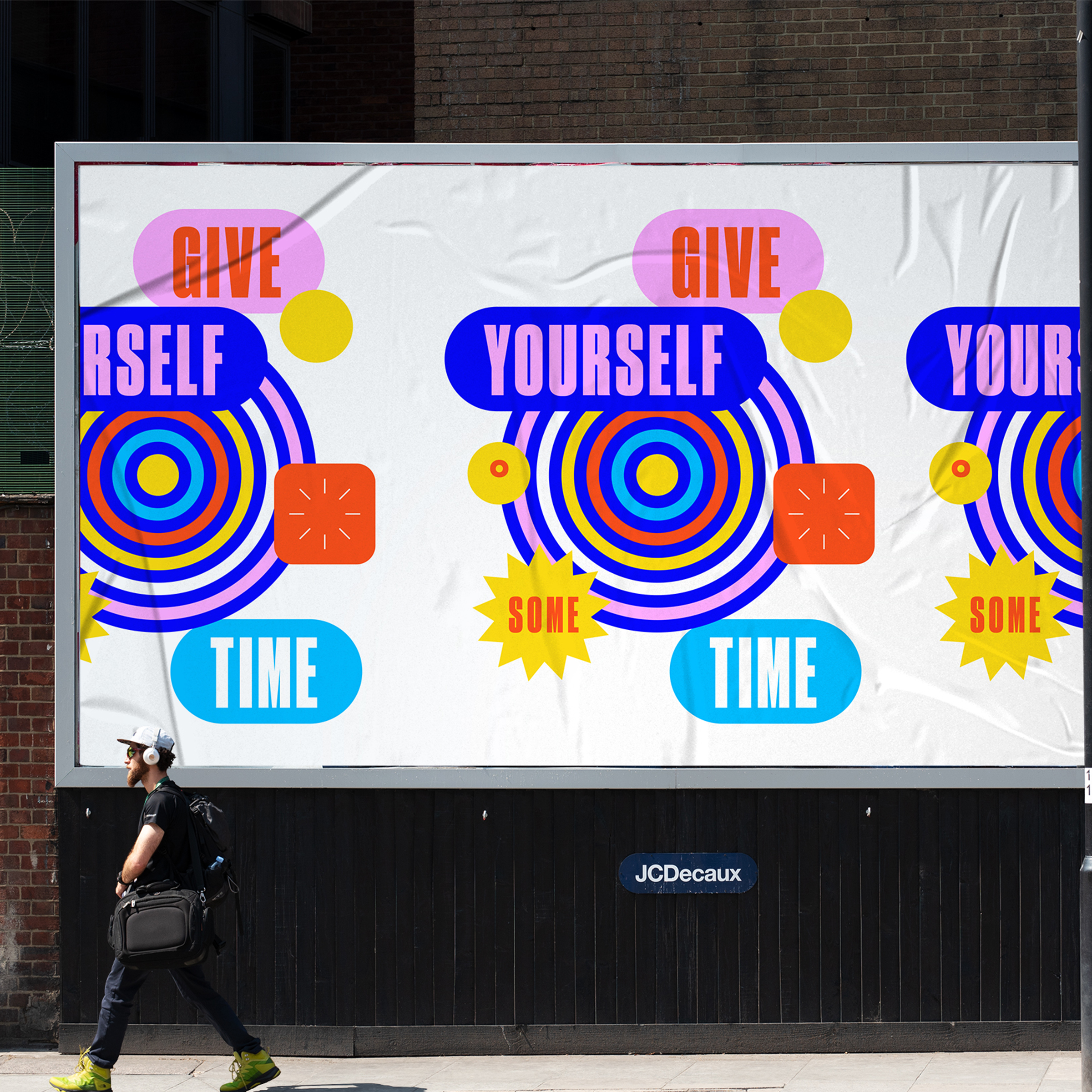 """A photograph of a person walking in front of a graphic billboard that repeats the phrase """"Give Yourself Some Time"""" in bold, bright colors."""
