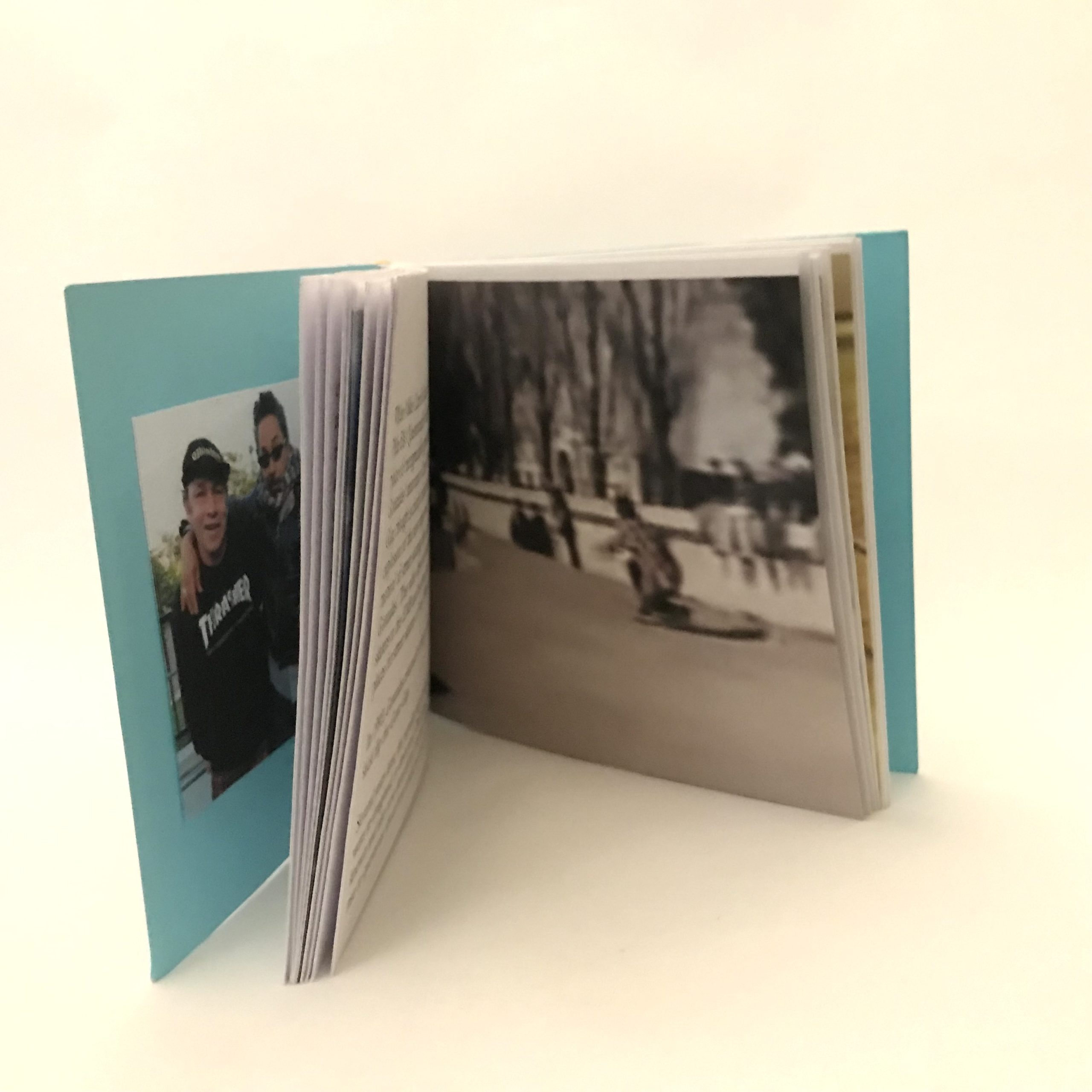 Artist's book standing upright and open on white background. On the front inside cover is a photograph of two people. The person on the left is wearing a black baseball hat and sweater with the words 'Thrasher' in white. The person on the right has their arm around the person on the left. They are wearing sunglasses, a scarf and a leather jacket. Other opened pages depict unreadable text and a screen capture of a person compressed on a skateboard after landing a trick. People in the background are standing and sitting on ledges observing the trick.