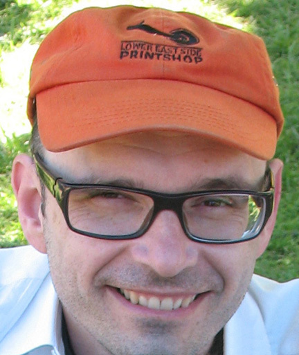 Headshot of Michael Bartalos. He is wearing an orange hat, glasses, and white collared shirt