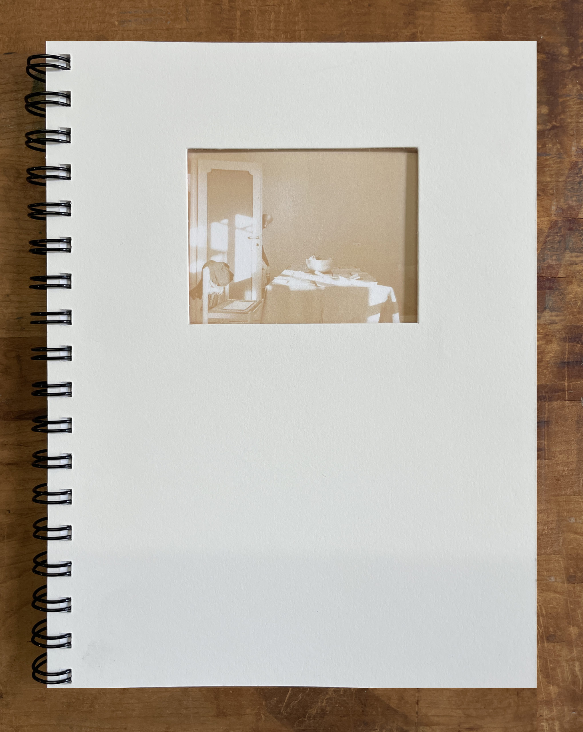 whit book cover with lavender coil binding and 3 by 4 inch window cuth through reveling a photo of a table